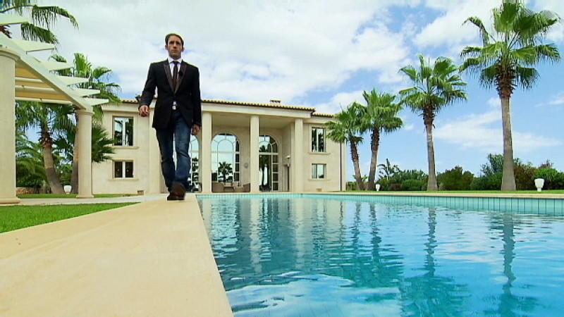 Makler Marcel Remus steht alleine am Pool