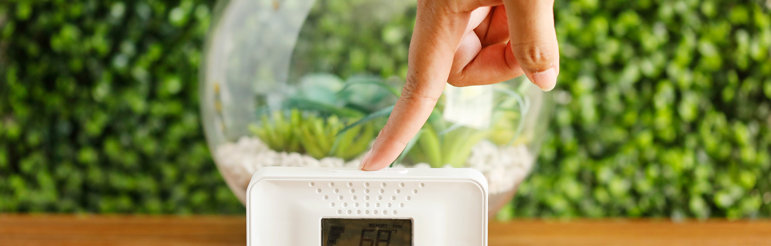 carbon monoxide tester with finger pushing the button