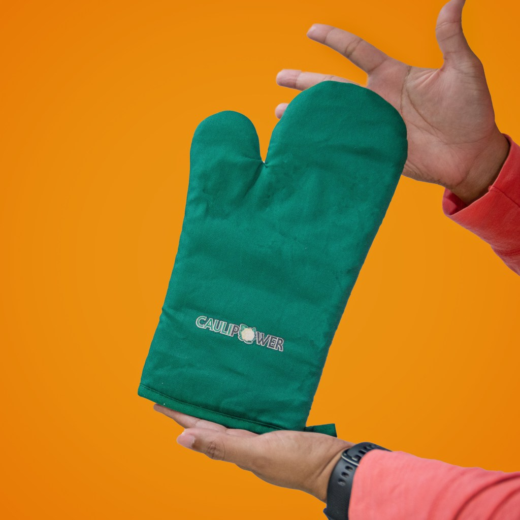 Woman holding Caulipower Green oven mitt in front of orange backdrop