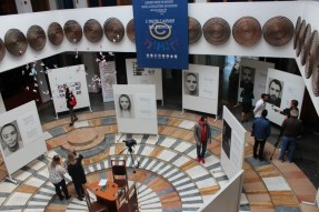 the images shows an exhibition of photogrpahs and text in an ornate circular room, and people looking at the exhibition