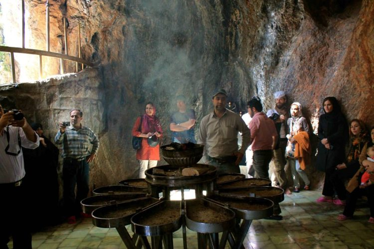 A tour guide stands in the middle of the shrine and explains the story of Hayatbanu and Chak Chak.