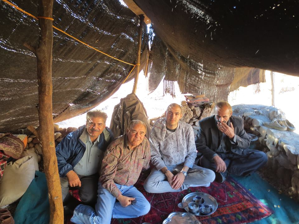The author (second from right) pictured sharing tea with his father (second from left) and some good friends in a Lori tent.