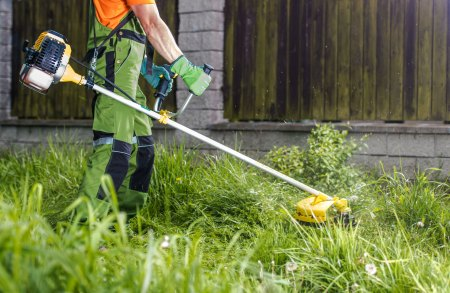 man using a gas powered string trimmer on his lawn