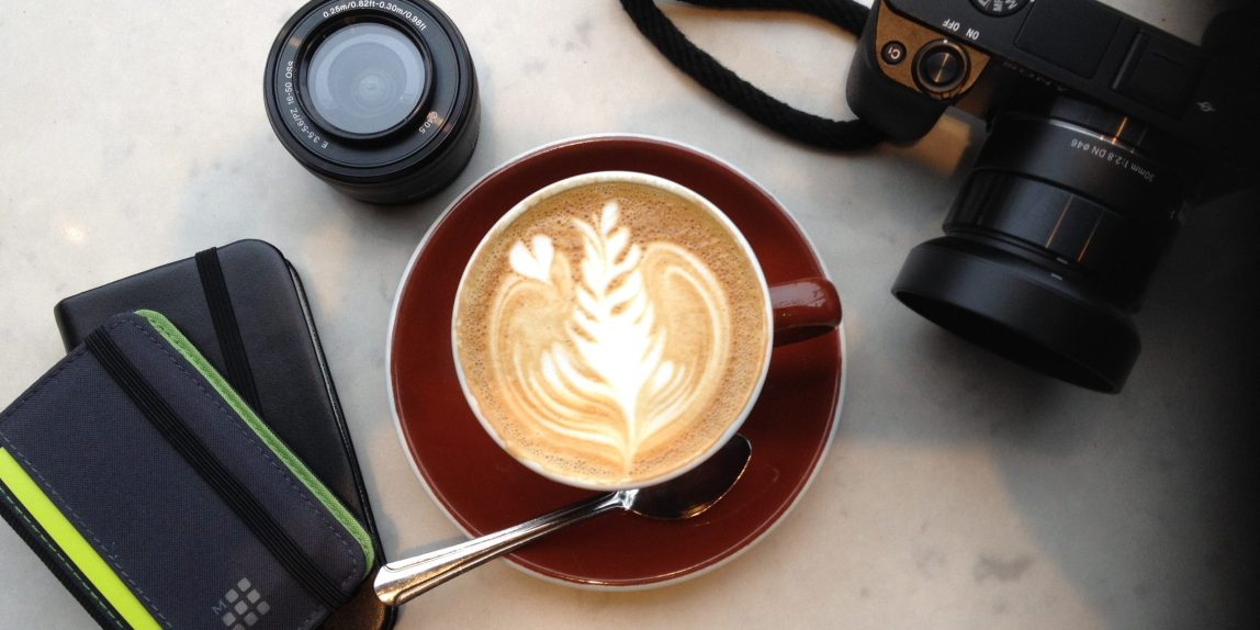 Center- cappuccino on a cafe table with moleskin in lower left, lens to its right and a sony a6000 camera in top right.