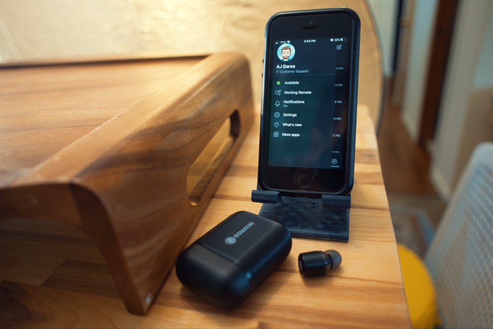 an iphone with black Rowkin earbuds on a wood table