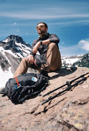 AJ on a mountain with a mountain behind him holding his black hiking had and his camera bag in front of him