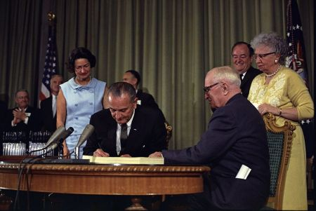 President Lyndon B. Johnson signing the Medicare Bill at the Harry S. Truman Library in Independence, Missouri. Former President Harry S. Truman is seated at the table with President Johnson. Photo: National Archives and Records Administration.