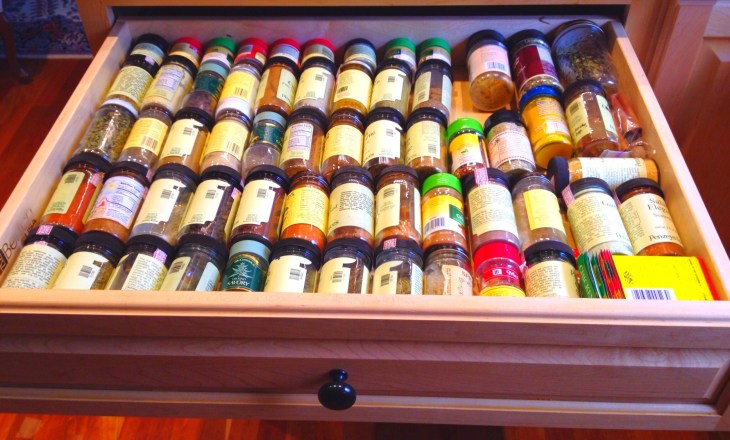 spice jars lay on their sides in a spice drawer