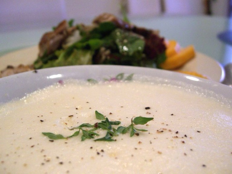 a bowl is filled with creamy avgolemono soup.