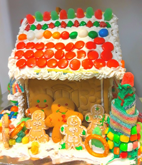 Icing, gumdrops, and candy pieces make a colorful roof on this gingerbread house
