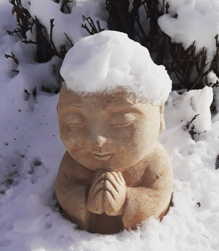 Buddha statue in garden covered with snow