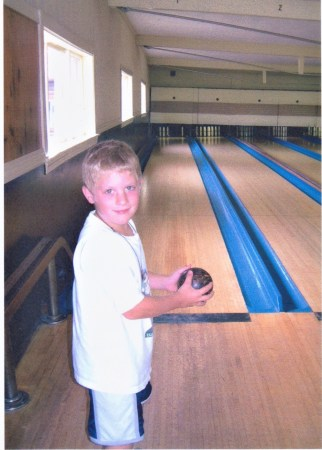Young boy getting ready to roll his bowling ball down the alley at duckpin bowling.