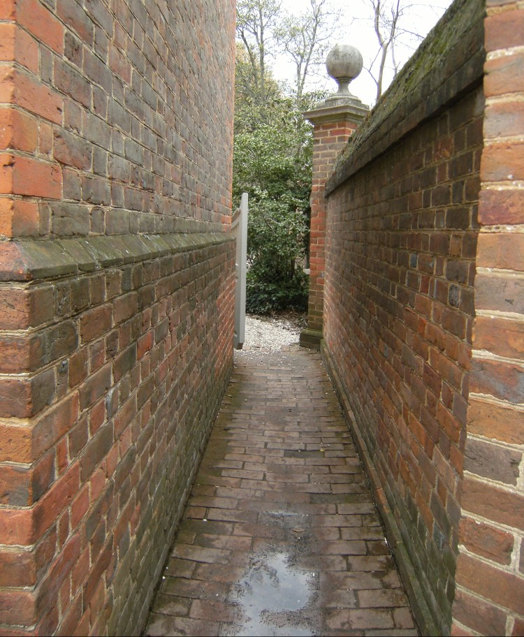 A brick wall stretches to the garden gate