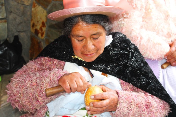 Andean woman carving a gourd