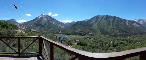 View from the deck includes lake, mountains, and a hummingbird