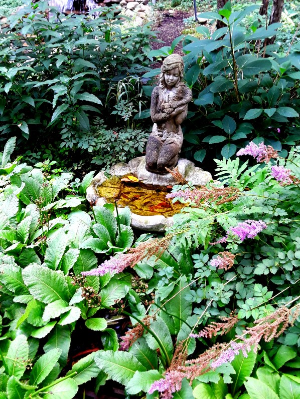 A fountain among primroses and astilbe