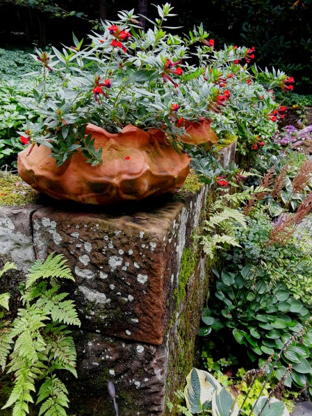 a stone pillar along the garden path is covered with lichen and moss