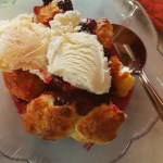 blackberry cobbler is warm and topped with vanilla ice cream