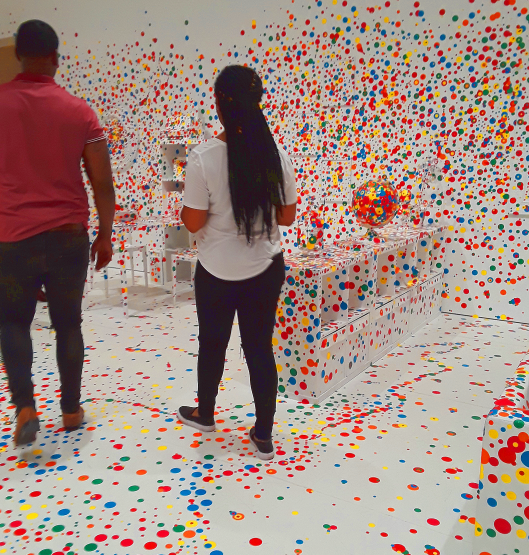 a couple walks through the all white room decorated with dot stickers