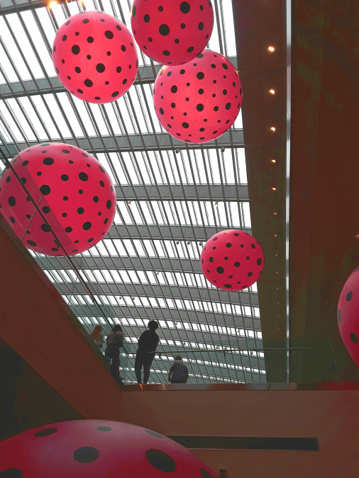 Large pink spheres covered in black dots hang from the atrium ceiling at the Cleveland Museum of Art
