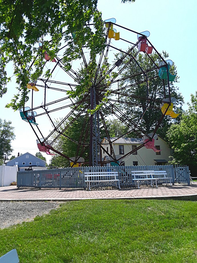 A Ferris Wheel with yellow, red, and blue cars.