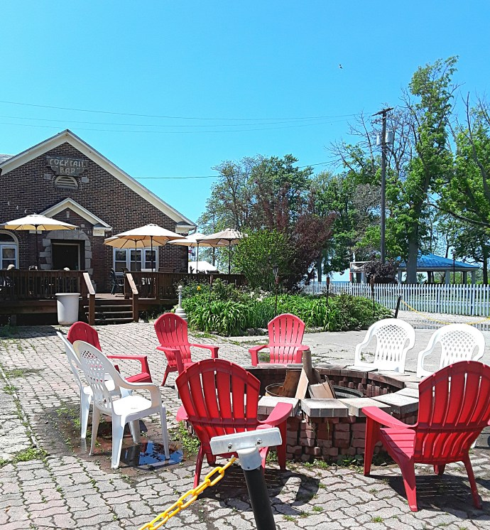 Patio seating outside of the ale house includes a fire pit.