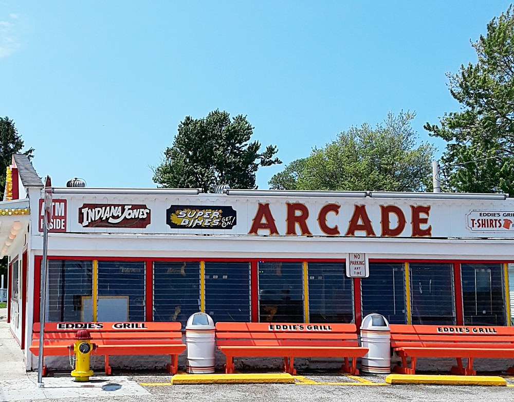 Arcade building is painted white with bright orange benches in front.