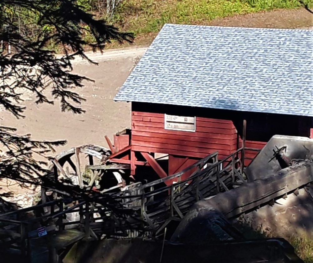 red sided mill building with wooden wheel