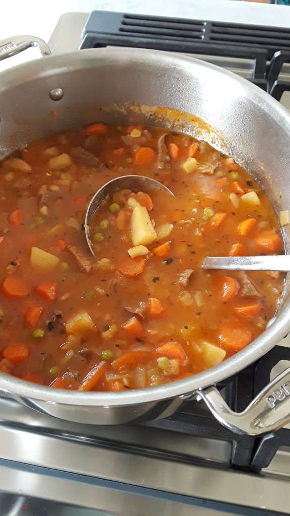 Vegetable soup is ladled from a large stainless steel pot