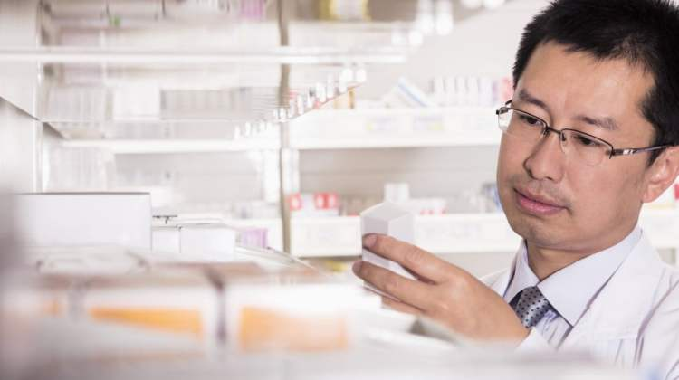 Pharmacy competency standards: pharmacist in dispensary takes down box and examines it