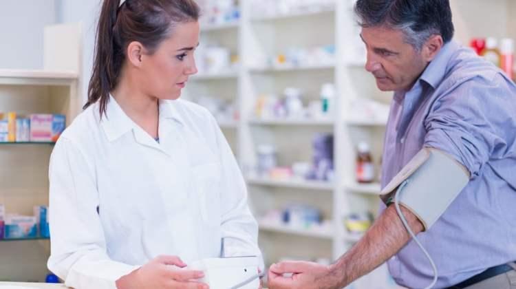 community pharmacies: pharmacist doing blood pressure check