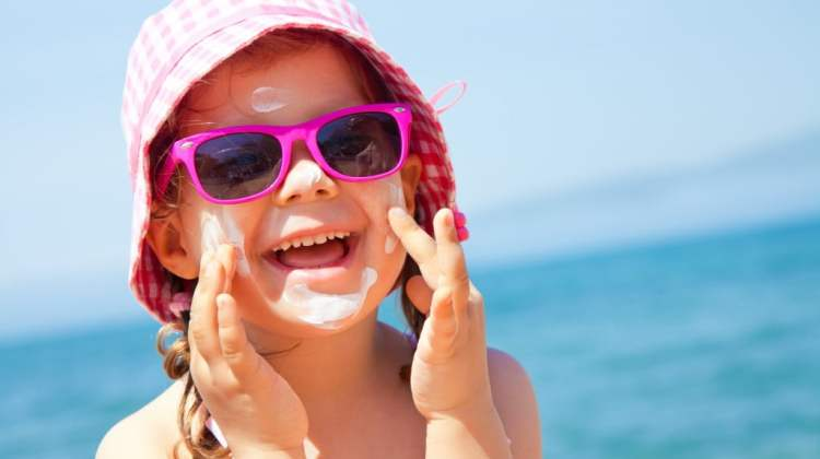 laughing girl at beach wearing big pink sunglasses