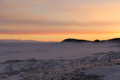 Sunset over the frozen Ross Sea at McMurdo Sound, and Hut Point in the distance.