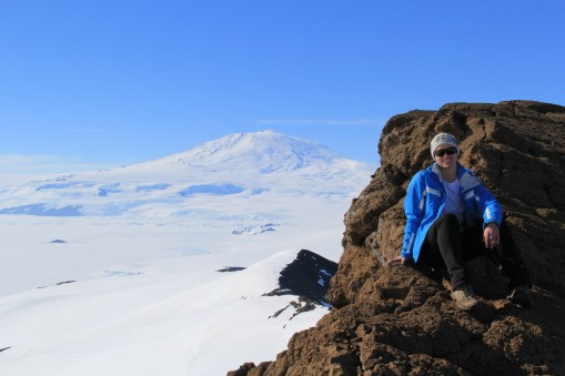 Bev, resting on Castle Rock with Mt. Erebus looming in the background. © A. Padilla