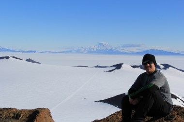 Abe, taking a rest on Castle Rock, with Mt. Discovery in the distance. McMurdo is hidden around the center of the picture, just below the white dome. © A. Padilla