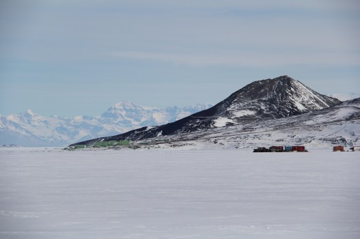 Ob Hill rises above Scott Base (at its base, in front) as the Royal Society Mountains stretch behind it in the distance. View from the Ross Ice Shelf. © A. Padilla