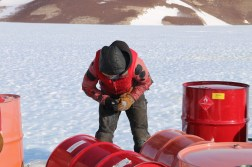 Fuel Operator Jamie McMillen inspects fuel barrels at the Odell Glacier fuel cache. © A. Padilla