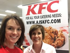 two women in front of a KFC catering sign