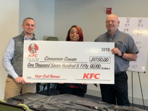 three people holding Cinnamon Cowan's End of Year bonus check