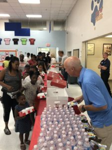 A middle aged man volunteering with KFC by handing out water bottles and juice boxes to attendees.