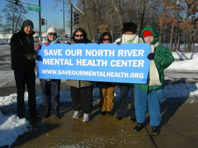 Protesters hold a banner saying: Save Our North River Mental Health Center www.saveourmentalhealth.org