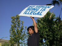 "A man holds a sign reading, ""no human being is illegal"""