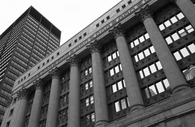 A black and white photograph looking up at Chicago City Hall from the street level