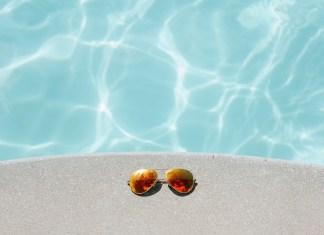 aviator sunglasses next to swimming pool