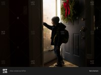Young boy opening the front door stock photo