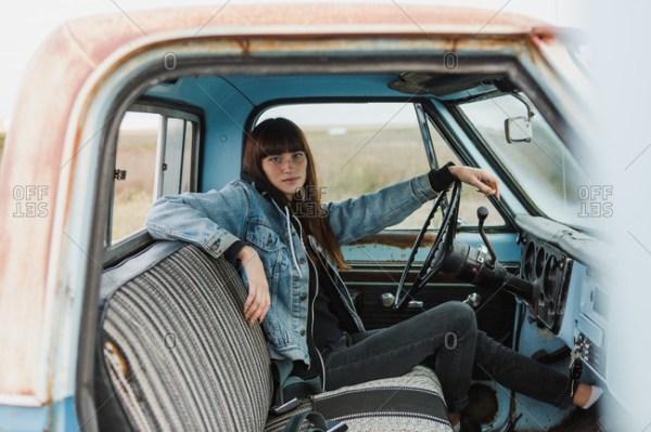 Passenger door view of woman driving a pickup truck stock