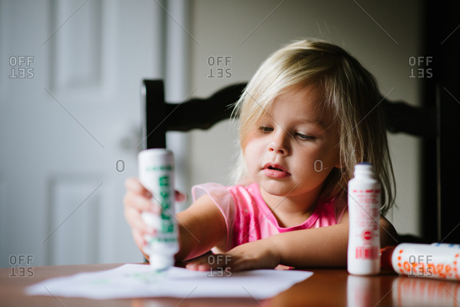 Young girl using glue sticks stock photo - OFFSET