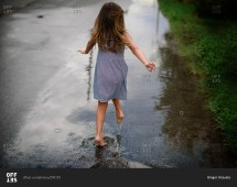 View Of Girl Running Barefoot Puddle