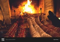 People in colorful socks and pajamas warm their feet in ...