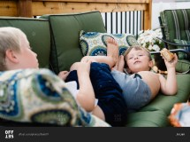 Two Boys Lying Couch And Roughhousing